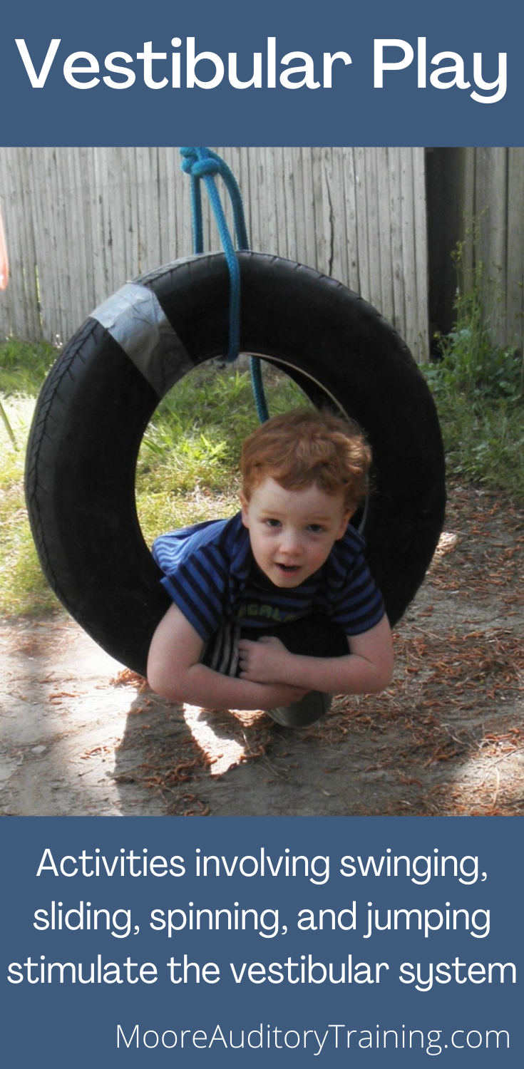 young boy on a tire swing