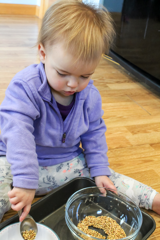 girl playing moving grain from one bowl to another