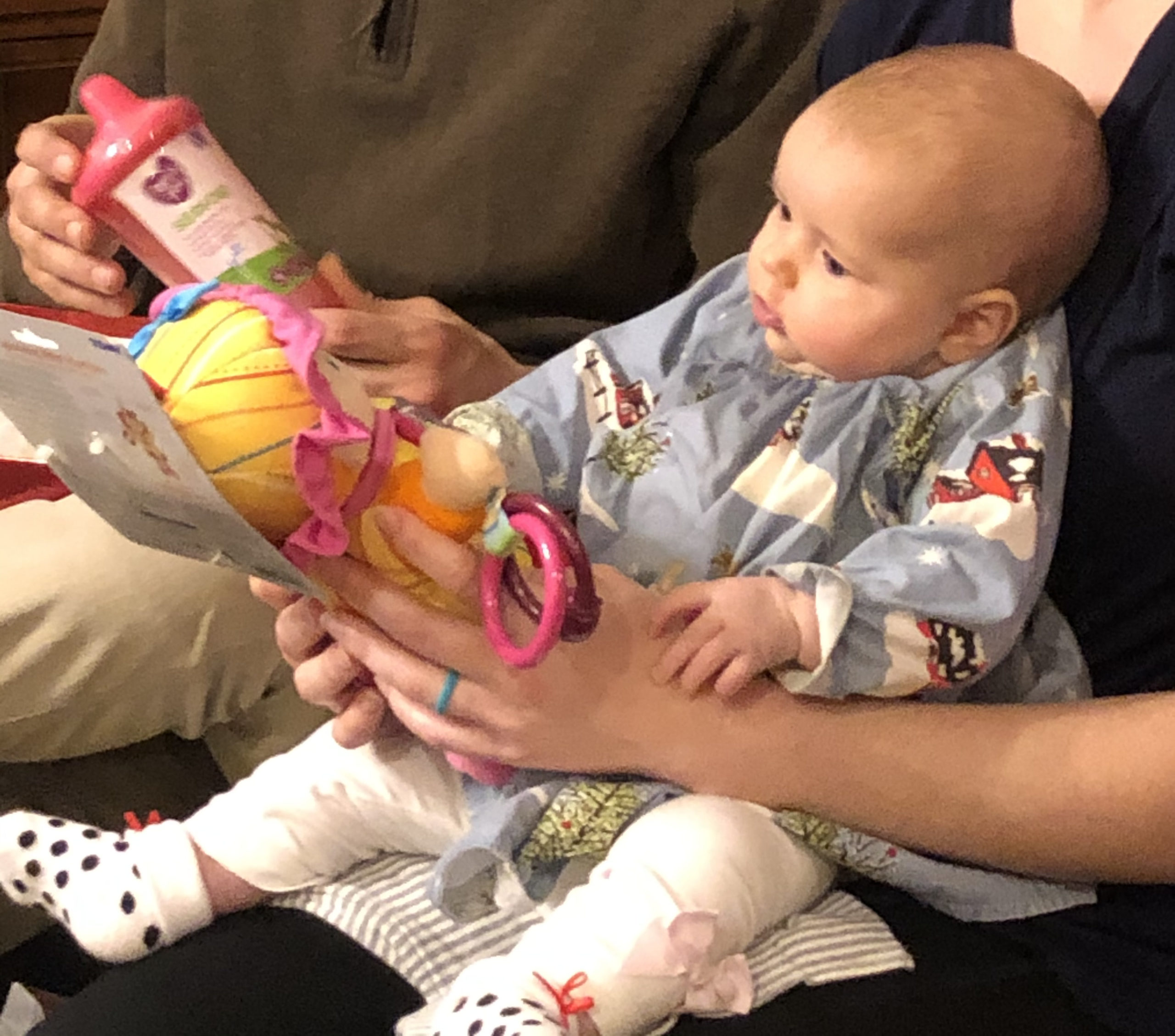 infant looking at the face of a stuffed doll with a yellow hat, outfit, and pink ribbon around the hat.