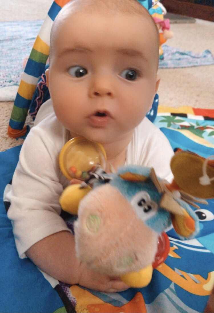 infant looking to far left with an awe expression on face. Infant's visual processing develops one milestone at a time.