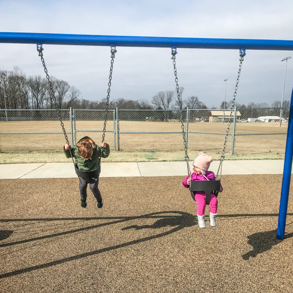 a little boy and girl swinging at a park