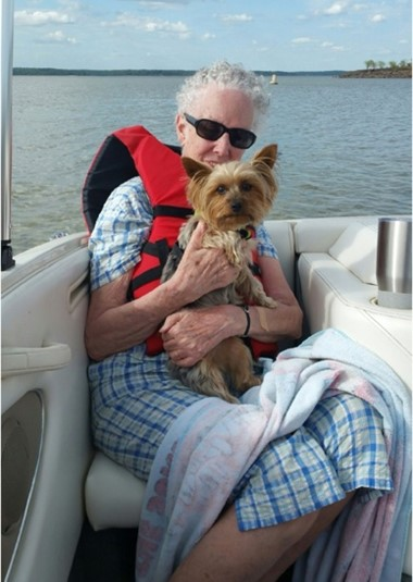 Older woman holding a Scottish Terrier dog while sitting on a seat in the back of a boat on the lake.