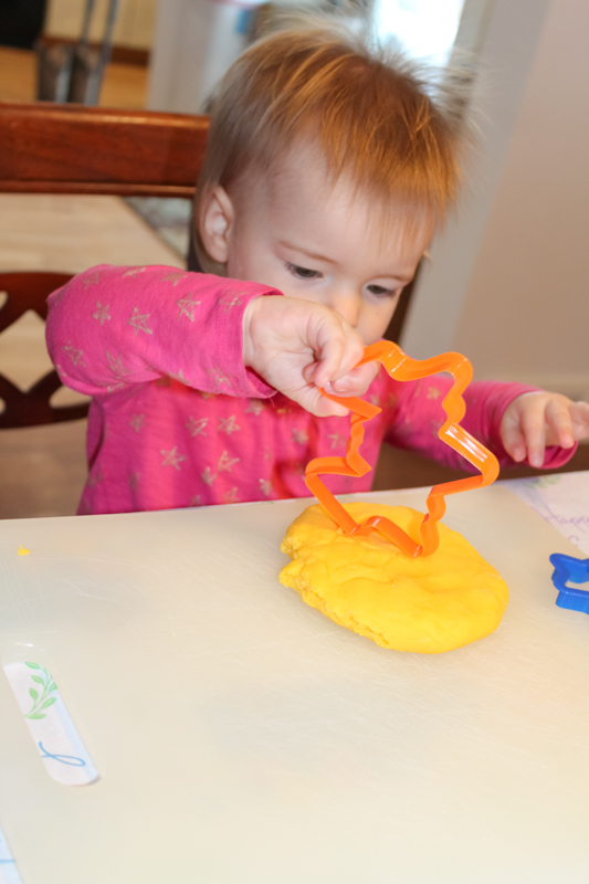 girl placing the edge of a cookie cutter into playdoh