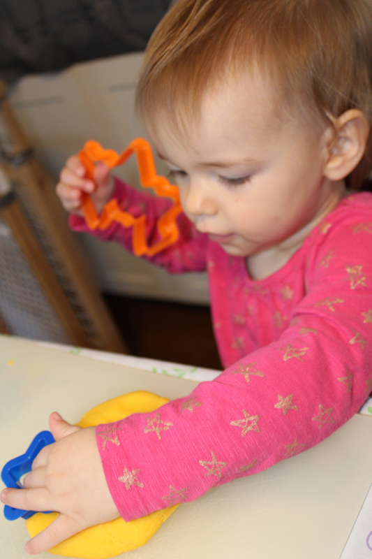 girl pressing a cookie cutter into a pad of gluten free playdoh which uses her vestibular system
