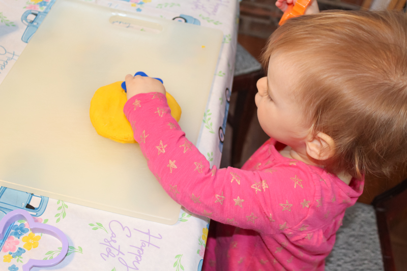 young girl using a cookie cutter to make a start in the gluten free playdoh