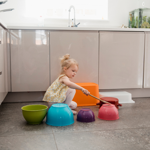 little girl tapping on pots and pans in the kitchen