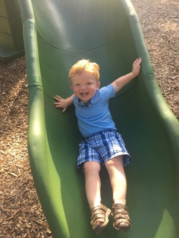 A little red-headed boy going down the slide while laughing