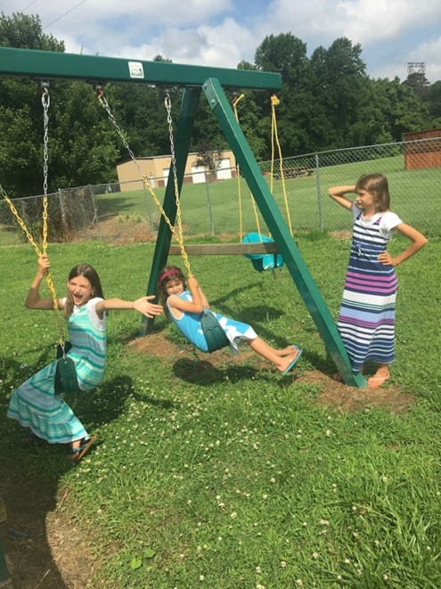 Two girls twisting and twirling round and round on swings on a swing set with a third girl watching and covering one ear.
