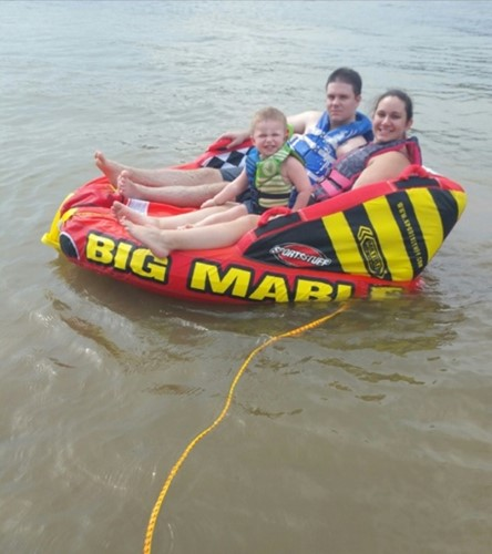 Two adults and one child on a water tube in a lake