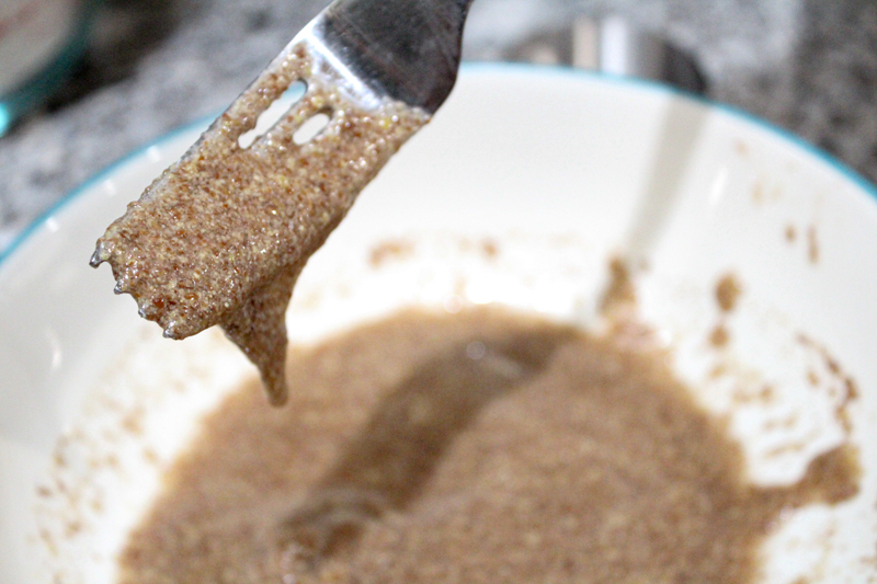 flaxseed egg mixture dripping off a fork held above a bowl