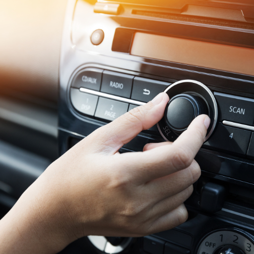 a hand turning down the volume in the car to demonstrate safe listening habits.