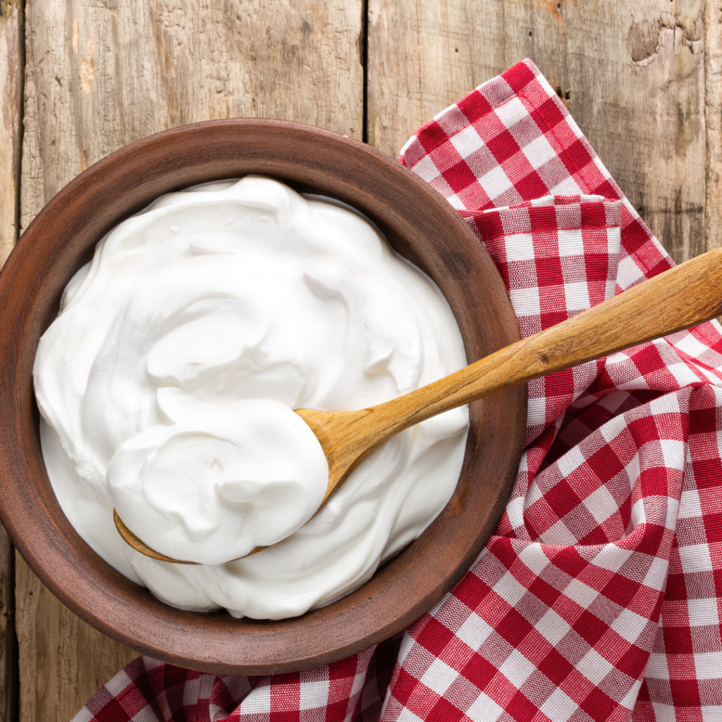 a wooden bowl of yogurt with a wooden spoonful of yogurt on top sitting on a rough wooden surface with a red and white checkered towel.