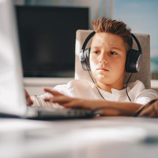 teen boy wearing headphones working on a laptop