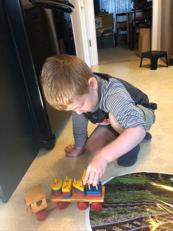 little boy building color patterns on a train block toy