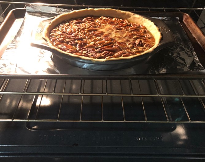 pecan pie in the oven on a cookie sheet