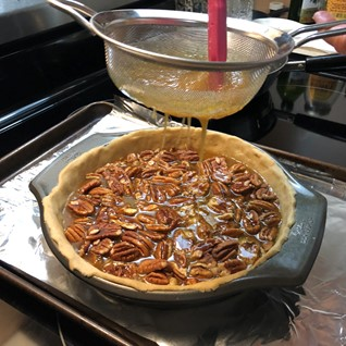 stirring mixture in a fine mesh strainer over a pecan pie