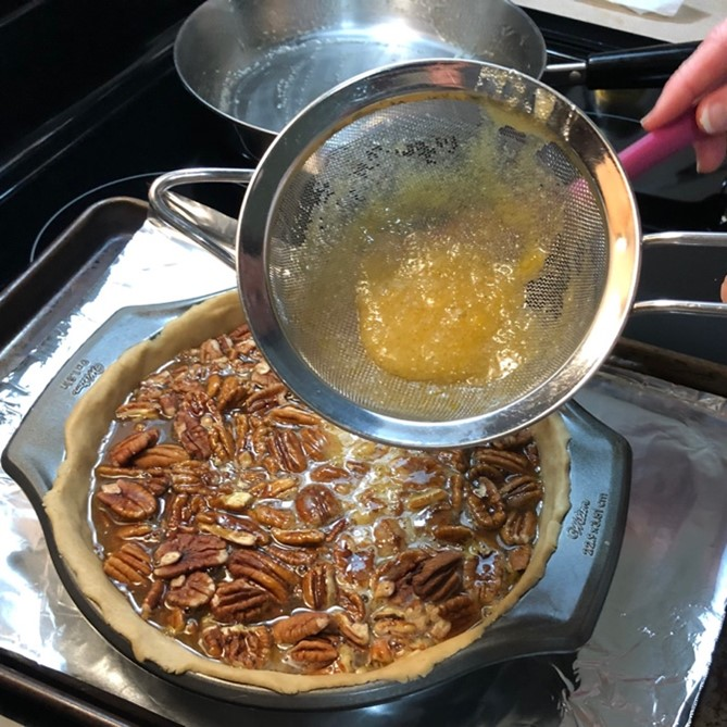 shows cooked egg bits left in fine mesh strainer from a pecan pie