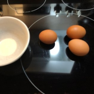 three eggs sitting on the stove top next to a bowl