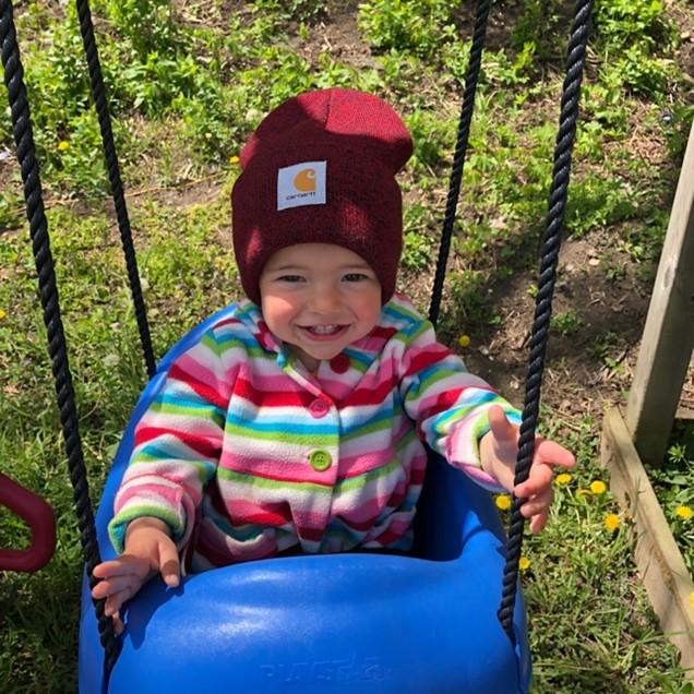 Little girl in a blue swing
