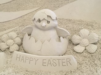 Sand sculpture of a chicken hatching from an egg with a flower on either side and a sign in fron tthat says happy easter.