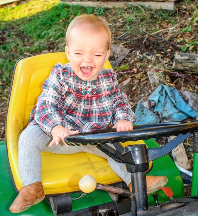 a one year old sitting on a John Deere lawn mower laughing with her eyes closed.