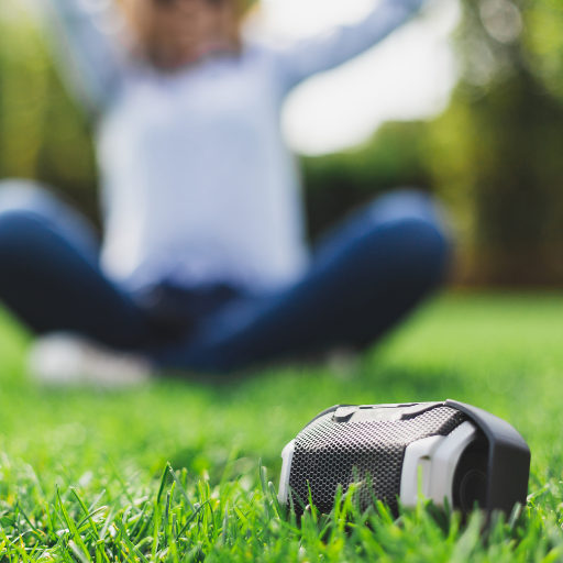lady sitting in the grass in the background listening to a portable speaker which is crisp and in focus