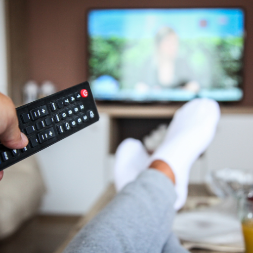 holding a tv remote pointed at the TV with feet up on the coffee table