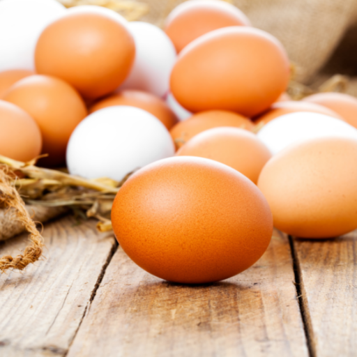 Pile of brown and white eggs sitting on a wood plank surface. Eggs in the background are sitting on a burlap sack. There is one brown egg in the foreground centered on the middle plank