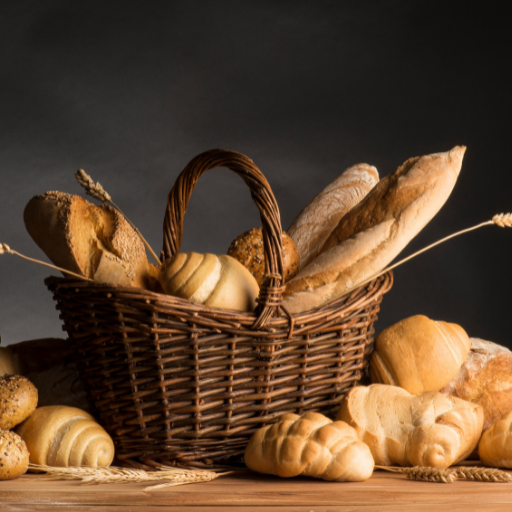 bread containing gluten which should be avoiding while shopping on an elimination diet. the bread is sitting in and around a whicker basket on a wooden table. The background is a dark gray making the light browns of the artisan breads stand out.