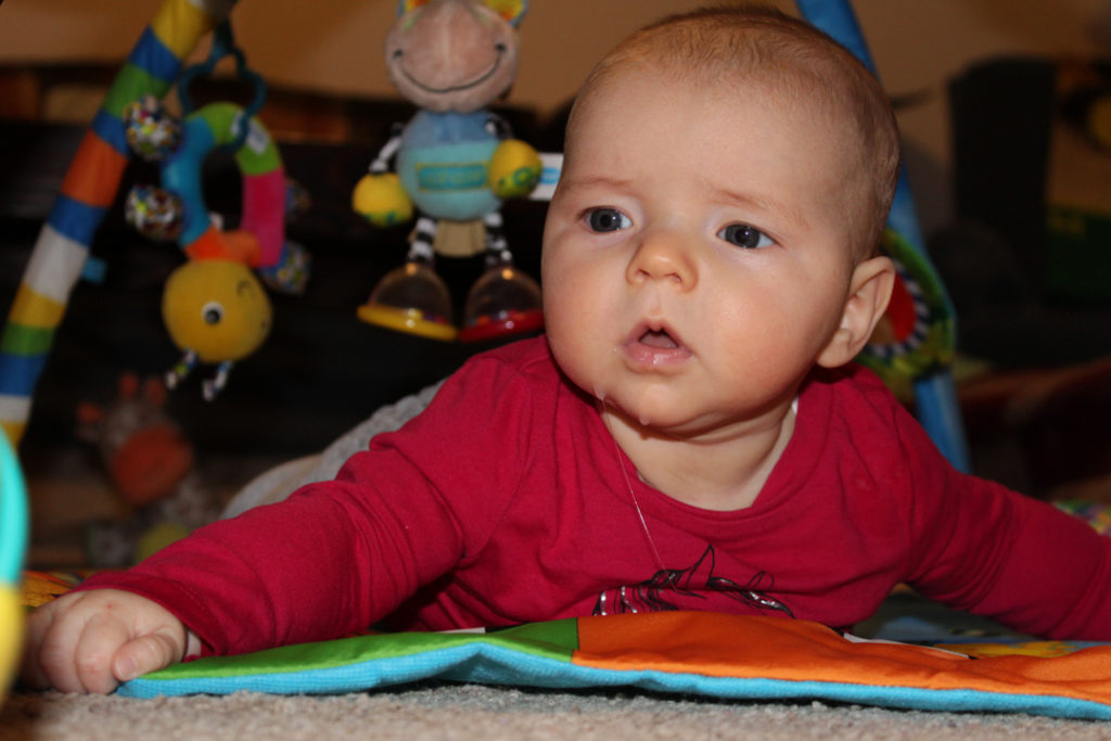 3 month old doing tummy time. Her hands are spread, her head is lifted, and her head and eyes are looking to the right at an object barely shown in the corner of the image.