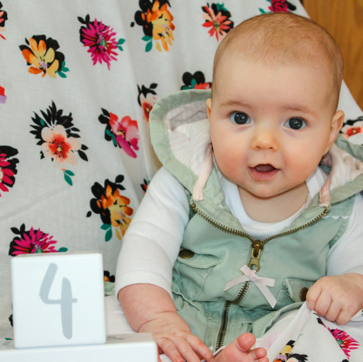 4 month old baby girl in a white long sleeve onesie with a light green vest on. She is sitting in the corner of a rocking chair covered in a flower blanker. There is a white block with a gray number four on it in front of her. The baby is slightly leaning forward grasping the blanket with her left hand looking at the camera with both eyes moving in alignment.