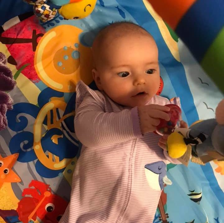 2 month old baby laying on her back in on a colorful play gym. her eyes are working together to inspect the bottom of a hanging toy that is above her. She is holding one foot of the toy with both hands. The baby's eyes do not have perfect eye movement alignment yet.