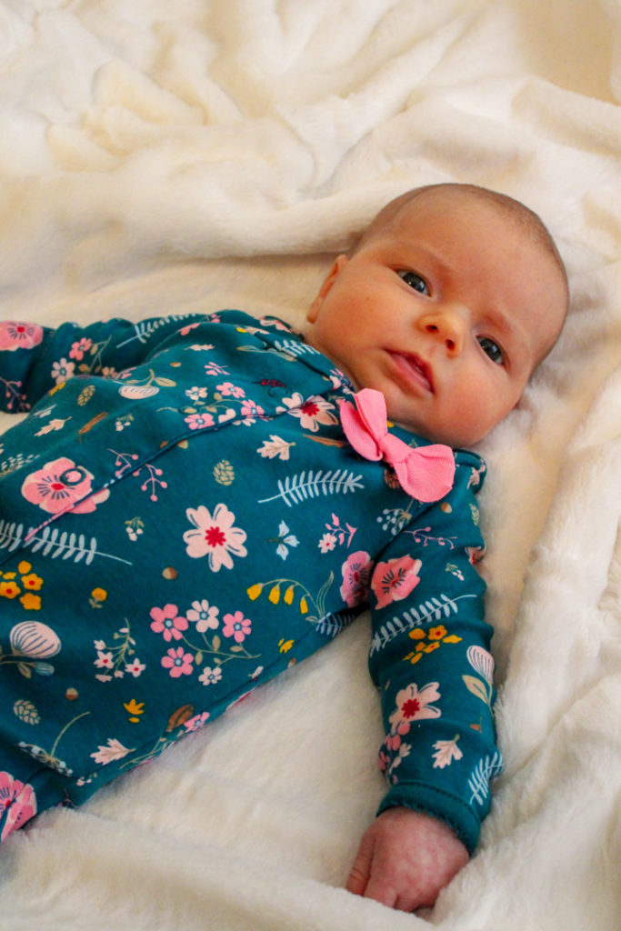 1 1/2 month old baby laying on a white blanket looking at the camera. She is wearing a green outfit covered in flowers that are various shades of pink. The baby's eye movements skills are developing and at this moment her eyes are working together to look at the camera.