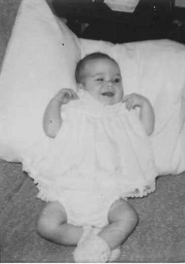 Infant laying against a pillow on the floor. Image shows poor development of baby's eye movements. One eye is clearly open and the other is half closed as she focuses on something outside of the photo.